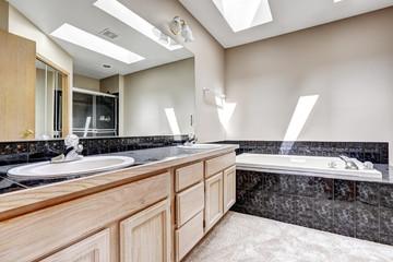 Bathroom with granite tile trim and skylight
