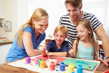 Parents Painting Picture With Children At Home