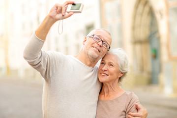 senior couple photographing on city street