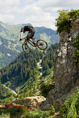 Mountainbiker jumping from a rock