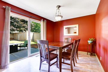 Dining area with bright red walls and walkout patio