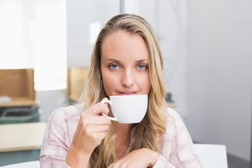 Businesswoman holding coffee mug and smiling