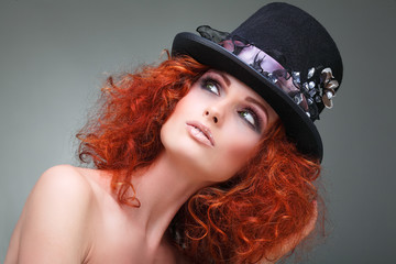 Portrait of beautiful redheaded girl in a black hat on a grey