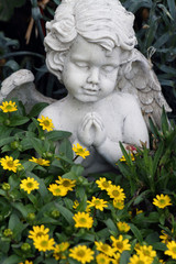 little praying angelic figure among the growing flowers on tomb