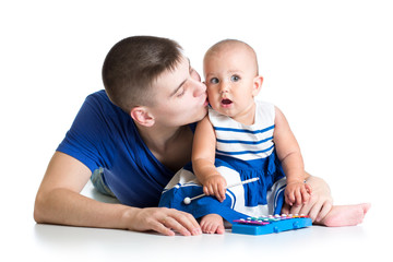 Young father and baby girl having fun with musical toys. Isolate