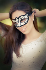 Portrait of a woman preparing for a masquerade bal