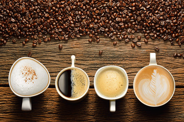 Foto op Aluminium Koffiebonen Variety of cups of coffee and coffee beans on old wooden table
