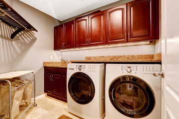 Modern laundry room with cabinets and granite top