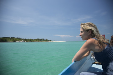 Blonde woman travels on a small boat on green water