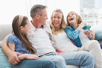 Smiling parents and children sitting together on couch