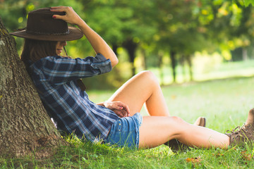 Cowgirl lies on field relaxing and enjoy the nature