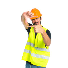 Workman focusing with his fingers on a white background