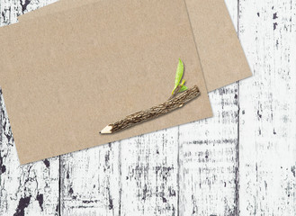 Brown paper and pencil on white wooden background