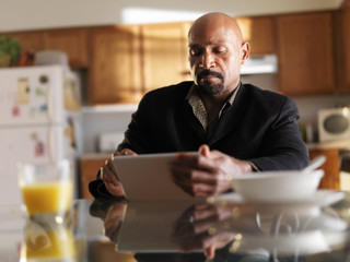 mature african man with tablet in kitchen and breakfast
