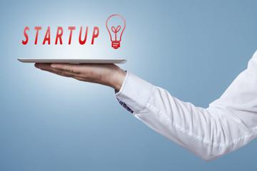 Hand hält Tablet darüber das Wort Startup mit Glühbirnen Symbol