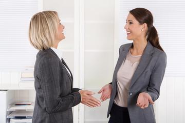 Zwei lachende erfolgreiche Frauen im Gespräch: Büro