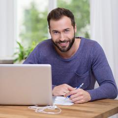 lächelnder typ sitzt mit laptop am tisch
