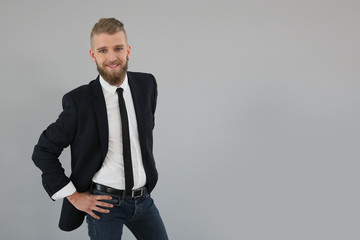 Confident young businessman on grey background