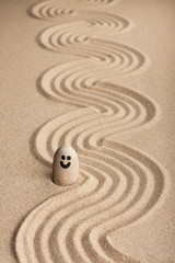 Stone smiley sticking out of the sand