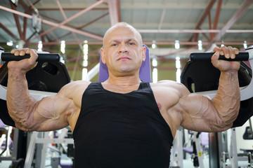 Bodybuilder in black jersey trains on exercise machine