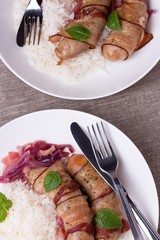 grilled bavarian sausages with rice and mint on white dish
