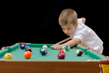 Beautiful boy playing billiard (pool)