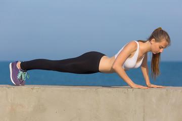 Pushups. Slim girl does morning exercises