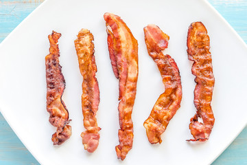 Fried bacon strips on the square plate