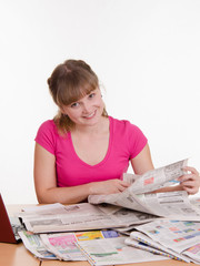 Girl looking for the right ad in newspaper