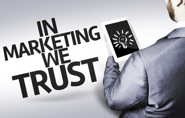 Business man with the text In Marketing We Trust