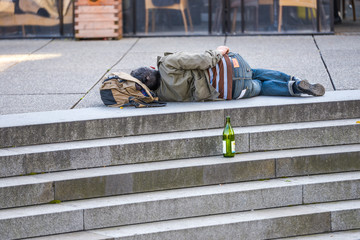 homeless sleeping on the top of stairs