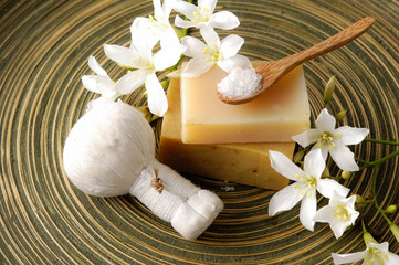 flower and massage ball with soap ,spoon on wooden plate