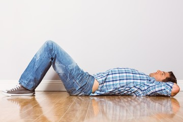 Young man lying on floor thinking