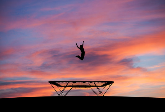 silhouetted man jumping on trampoline in sunset