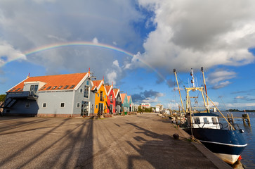 Fototapete - rainbow over harbor in fishing village Zoutkamp