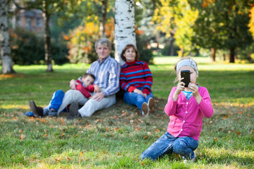 Happy family is on autumn park making pictures on phone