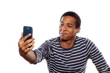 Smiling dark-skinned young man making selfie on white background