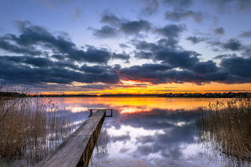Wall Mural - Purple Sunset over Tranquil Lake with Reed and Wooden Jetty
