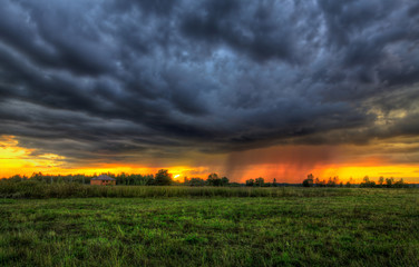 Дождевая туча на закате в поле