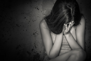 Black and white grunge image of a teen girl crying