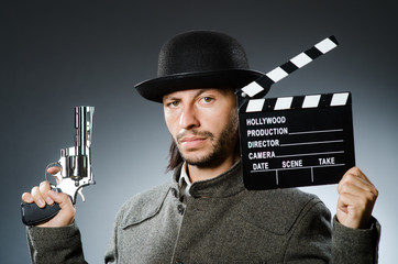 Foto op Canvas Surrealisme Man with gun and movie clapboard