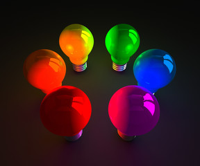 Colored glowing light bulbs standing on dark