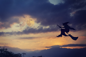 Silhouette of witch flying on broomstick at dramatic sky