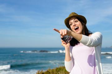Amazed funky woman taking photo to the sea