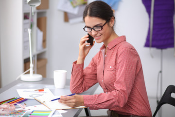 Young attractive female fashion designer working at office desk