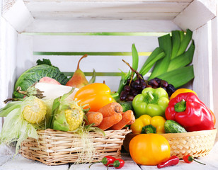 Vegetables in baskets on white wooden box background
