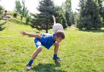 Boy with soccer ball in park on nature at summer.