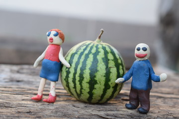 Plasticine man and woman near a watermelon