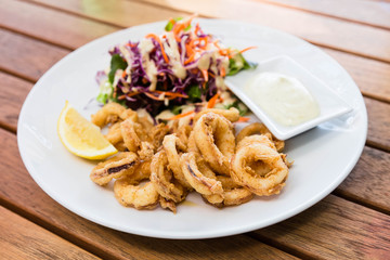 Deep fried calamari or squid with sauce on wooden table