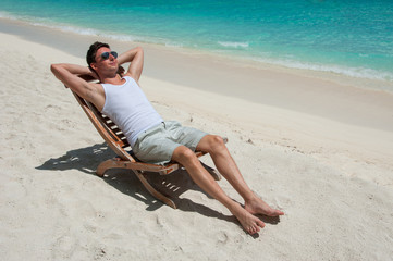 Man in chair sunbathing on the beach near the sea